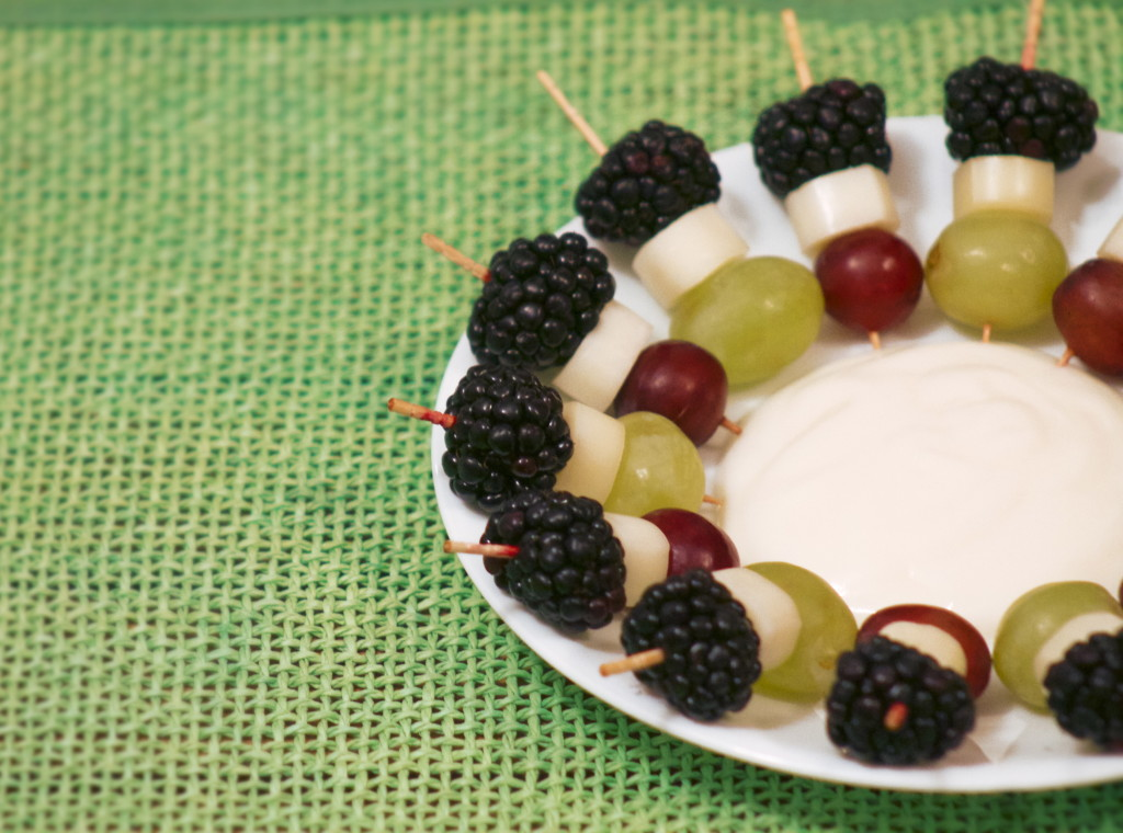 Mini fruit and cheese kabobs accompanied by yogurt for dipping.