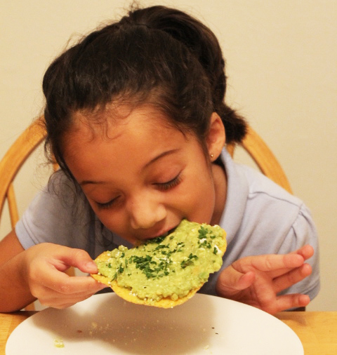 girl eating guacamole tostada