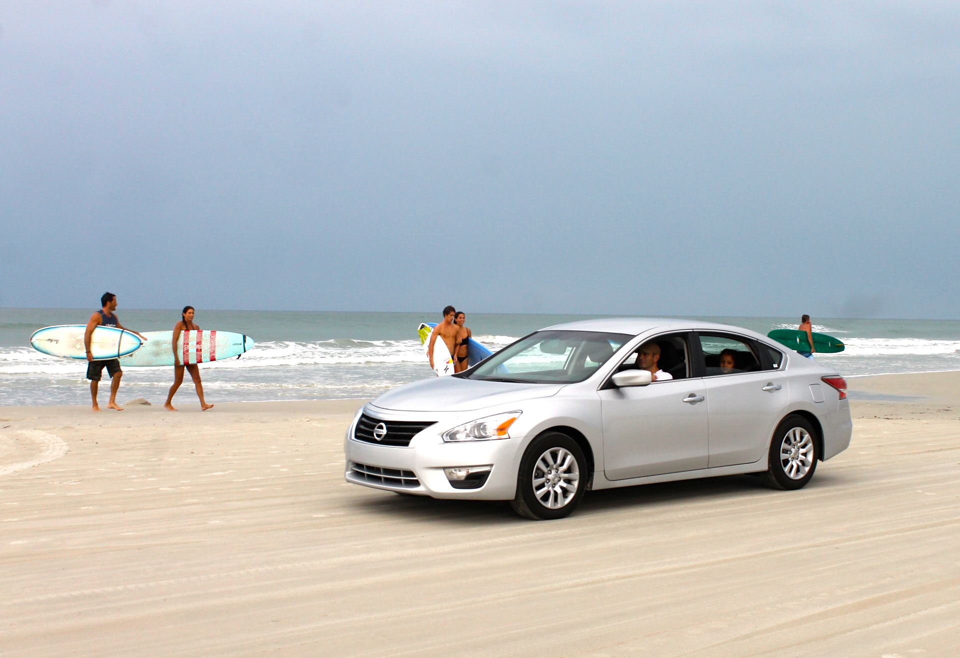 car on the beach with surfers in background at New Smyrna Beach