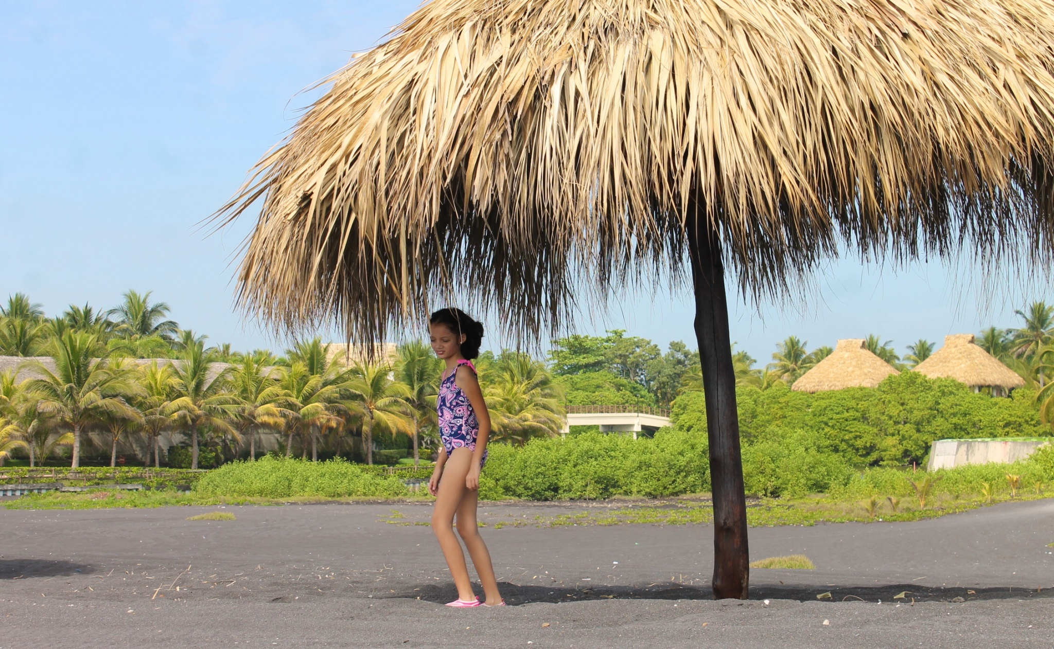 girl under a rancho in the black sand beach in Guatemala