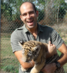 man carrying baby tiger