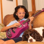 girl playing guitar with dog