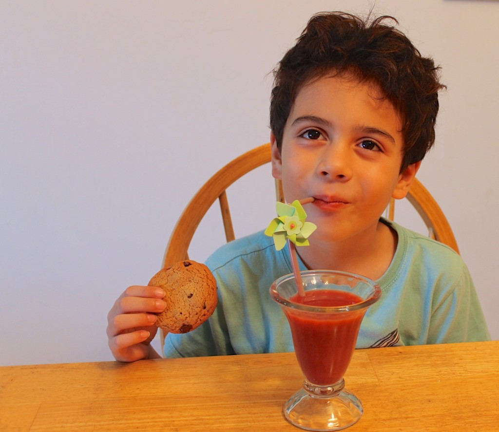 After school snacking. drinking Naked Juice and eating a Fiber One chocolate chip cookie.