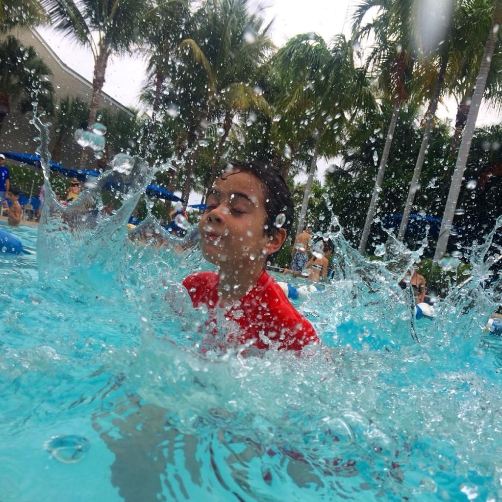 boy splashing in pool in South Seas Island Resort