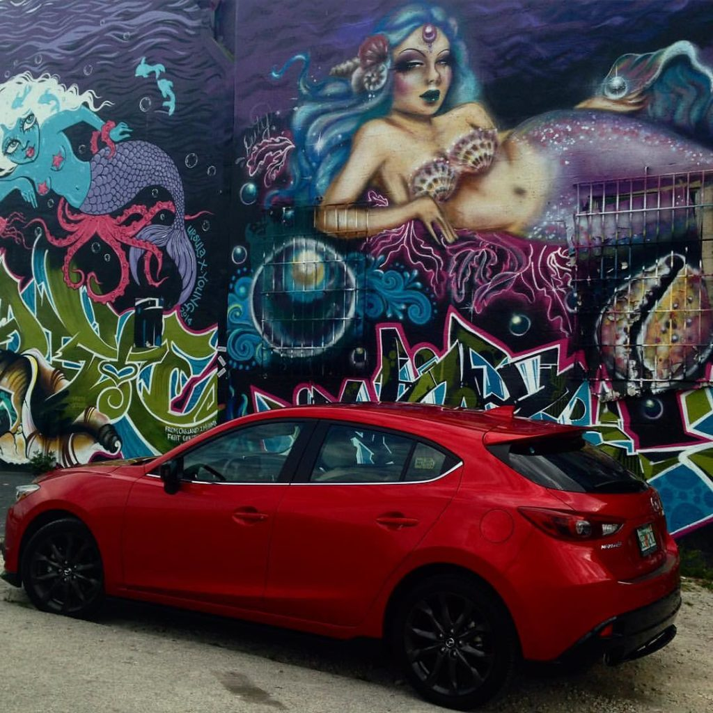 red Mazda 3 in front of street art