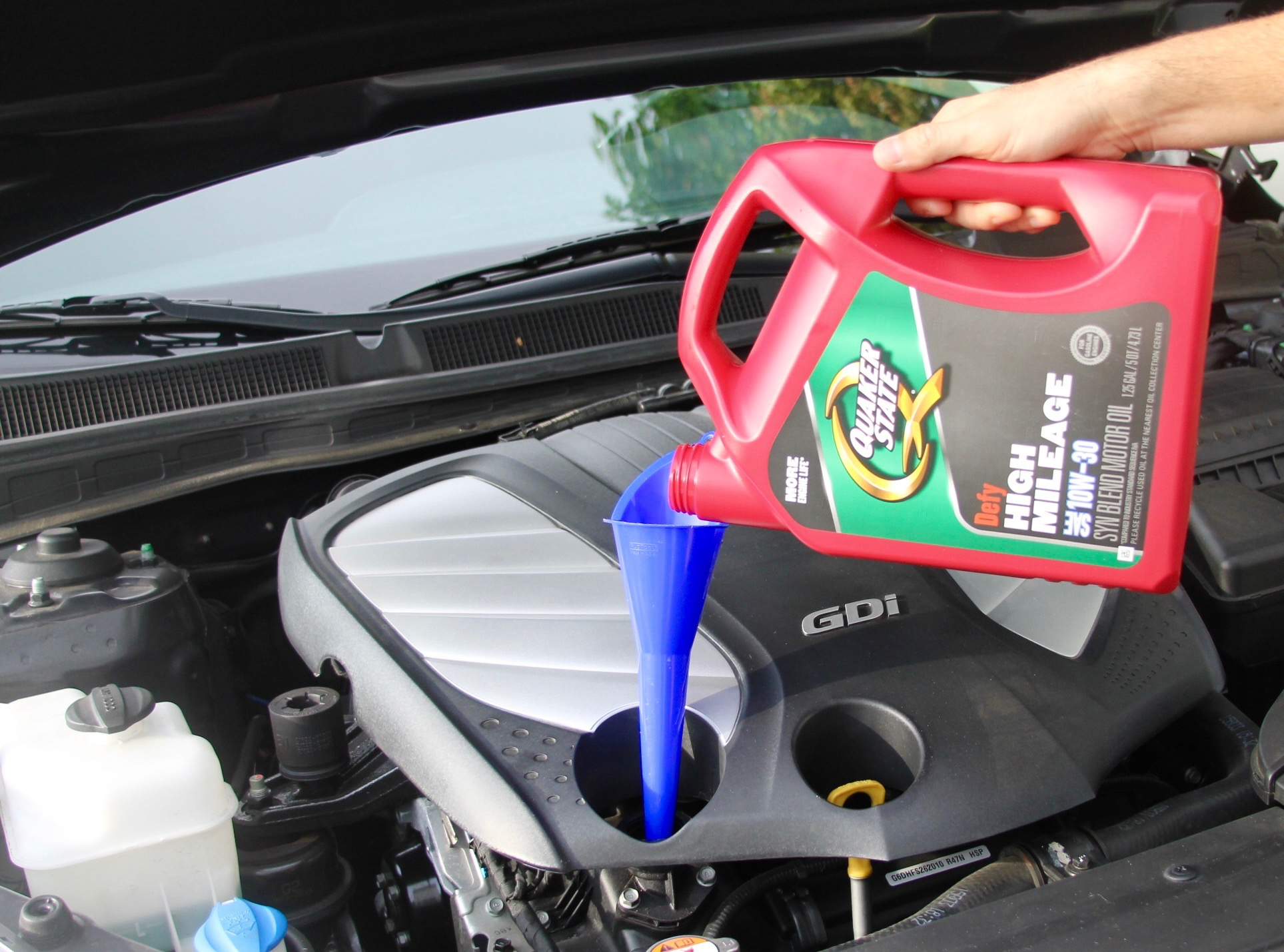 changing the oil on a car with Quaker State oil